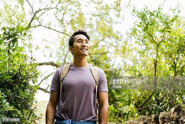 Confident smiling hiker standing against trees