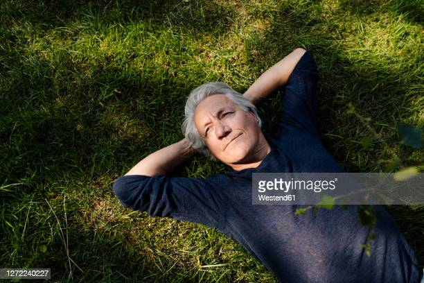 confident smiling man lying down in field - lying down stock-fotos und bilder