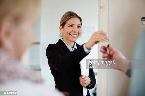 confident smiling realtor giving house keys to couple - datortangent bildbanksfoton och bilder