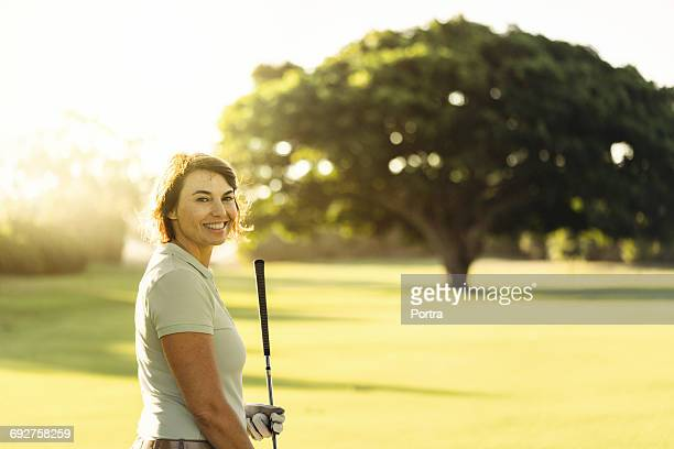 Confident smiling woman holding golf club