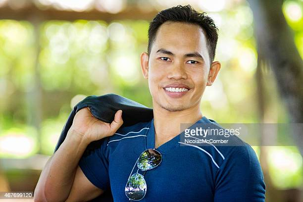 Confident smiling young Indonesian man portrait with sunglasses on t-shirt