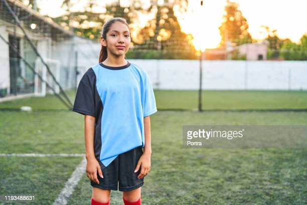 confident soccer girl standing on sports field - sports jersey stock pictures, royalty-free photos & images