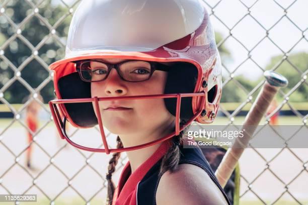 Confident softball player wearing helmet in dugout