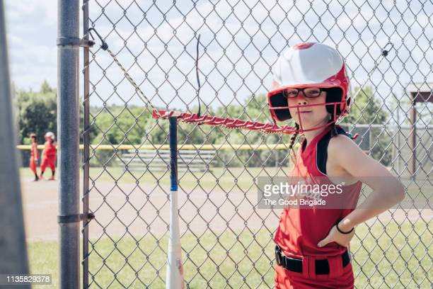 confident softball player wearing helmet in dugout - sports dugout stock pictures, royalty-free photos & images