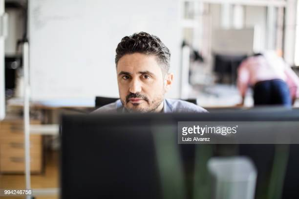 Confident software programmer sitting at office