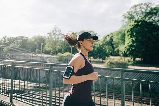 Confident sportswoman listening music through in-ear headphones while jogging on bridge in city - gettyimageskorea