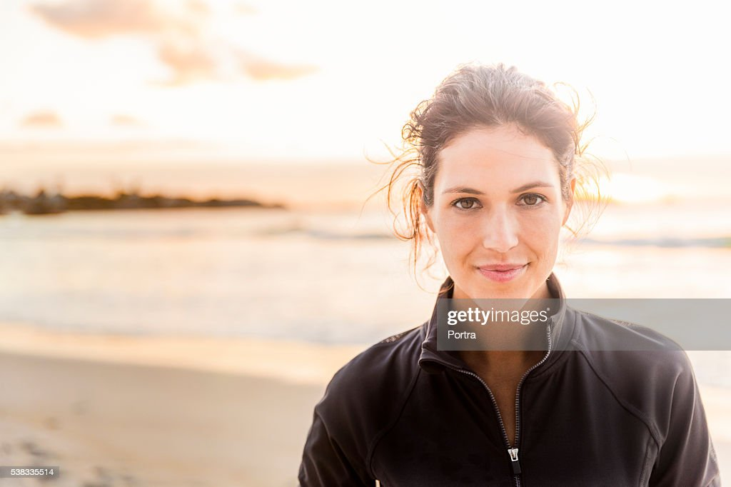 Confident sporty woman at beach : Stock Photo