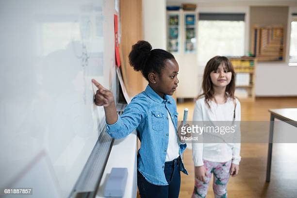 Confident student explaining while standing with classmate against whiteboard