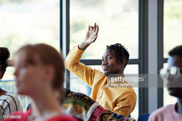 confident student looking away with arm raised - q&a stock pictures, royalty-free photos & images