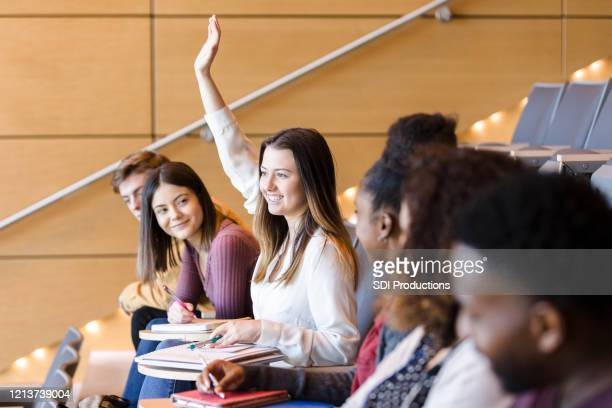 zekere student die hand tijdens klasse opheft - theaterzaal stockfoto's en -beelden
