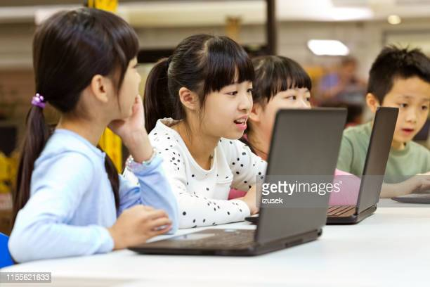 confident students using laptops in classroom - izusek stock pictures, royalty-free photos & images
