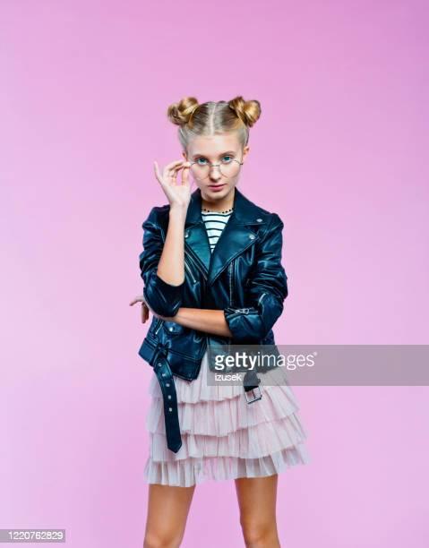confident stylish teenege girl peeking over eyeglasses - izusek imagens e fotografias de stock