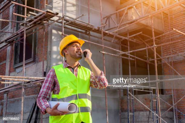 Confident supervisor in hard hat holding blueprint and talking on the mobile phone while standing outdoors