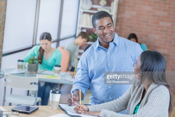 Confident teacher helps student in student lounge