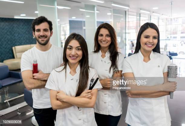 confident team of hairstylists at a hair salon looking at camera smiling with arms crossed - beautician stock pictures, royalty-free photos & images