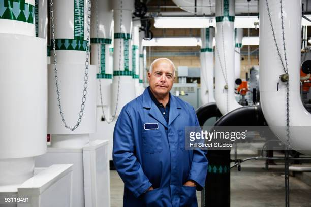 Confident technician standing in industrial plant