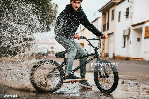 confident teenage boy splashing water in puddle while cycling on street during rainy season - teenagers only stock pictures, royalty-free photos & images