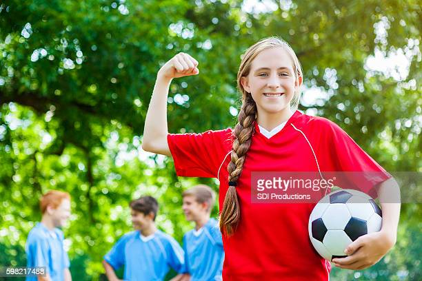 Confident teenage female soccer player flexes muscles at practice