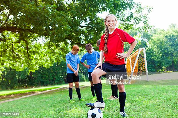 Confident teenage female soccer player poses with ball