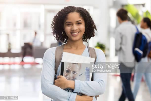 高校のロビーで誇らしげに立っている自信を持っている 10 代の少女 - 輪っかのイヤリング ストックフォトと画像