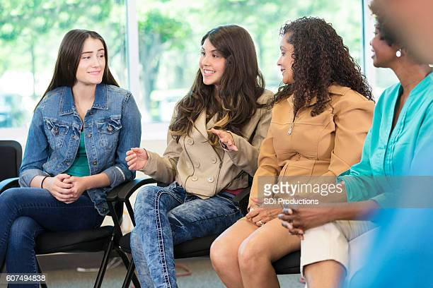 Confident teenager and her mother in discussion group