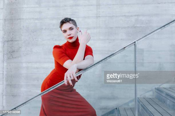 confident trans man wearing red dress standing on steps against wall - transgender stock pictures, royalty-free photos & images