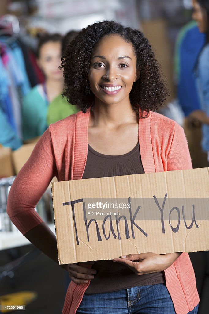 """Confident volunteer at food bank holding """"""""thank you"""""""" sign : Stock Photo"""