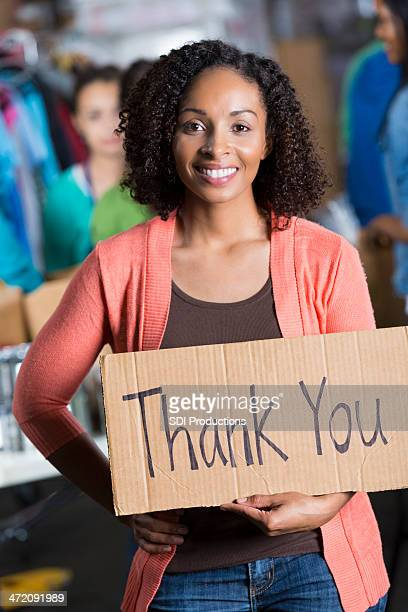 "Confident volunteer at food bank holding """"thank you"""" sign"