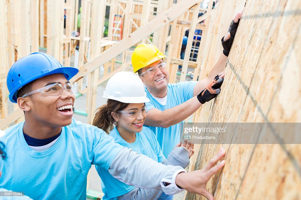 Confident volunteers build wall in charity home : Stock Photo