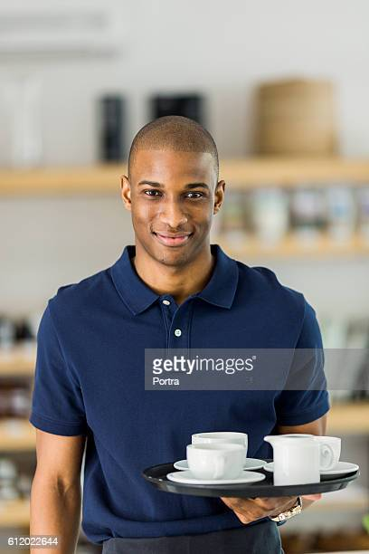 Confident waiter carrying cups on tray in cafe