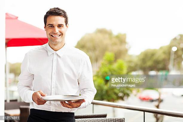 Confident Waiter With Serving Tray Smiling In Restaurant