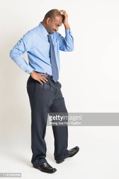 confident well-dressed businessman standing against white background - hand on hip stock pictures, royalty-free photos & images