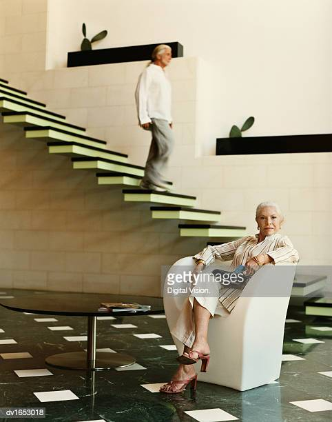 Confident Well-Dressed Senior Woman Sits in an Armchair in Her Modern Living Room, Her Husband Walking Down the Stairs