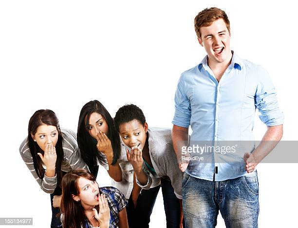 confident, winking young man indicates his size to shocked girls - foreskin stock pictures, royalty-free photos & images