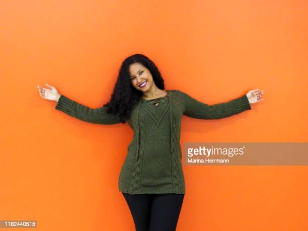 confident woman against orange background - arms outstretched stock pictures, royalty-free photos & images