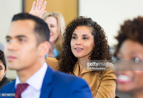 confident woman asks question during meeting - town hall meeting stock photos and pictures