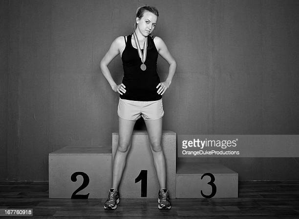 confident woman athlete in front of winners podium - winners podium stock pictures, royalty-free photos & images