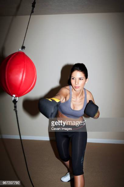 Confident woman boxing on punching bag against wall