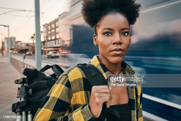 confident woman carrying backpack in city - aspirations stock pictures, royalty-free photos & images