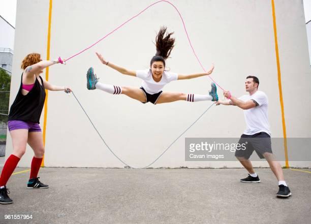 confident woman doing splits while performing double dutch against wall - split acrobatiek stockfoto's en -beelden