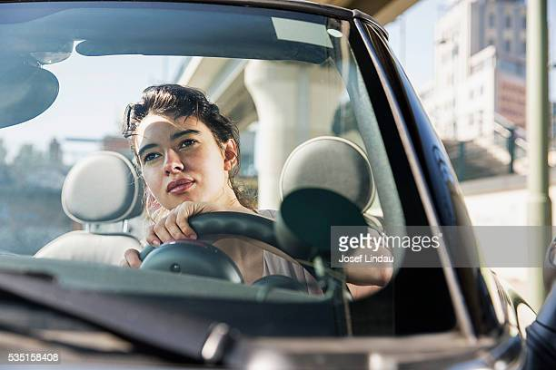 Confident woman driving her open-top car