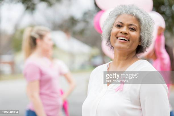 confident woman during breast cancer awareness event - survival stock pictures, royalty-free photos & images