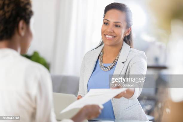 confident woman hands resume to potential employer - giving stock pictures, royalty-free photos & images