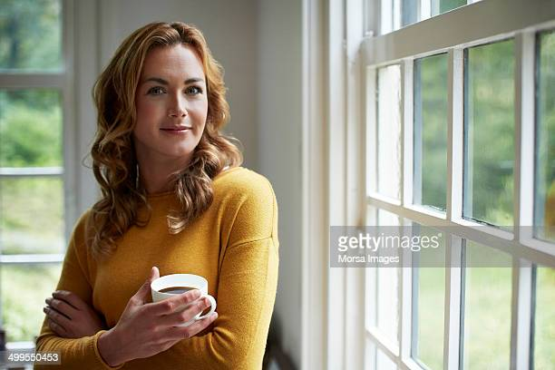 Confident woman having coffee in cottage