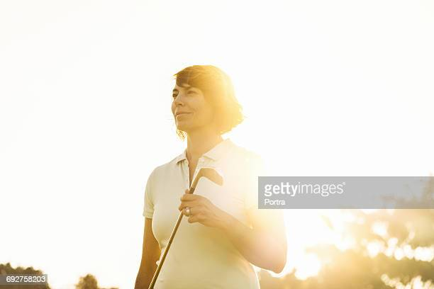Confident woman holding golf club on sunny day