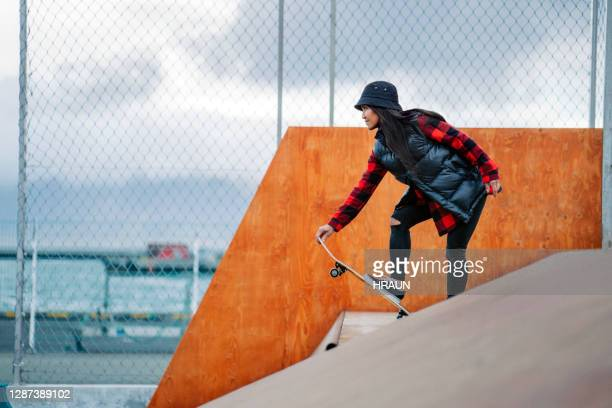 confident woman holding skateboard on top of ramp - skating stock pictures, royalty-free photos & images