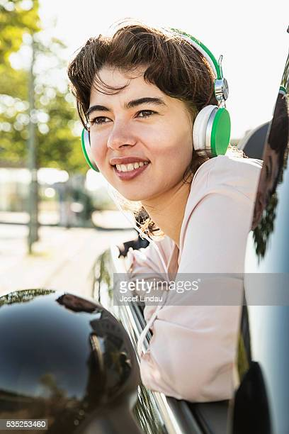 confident woman listening to music in open top car - open blouse stock photos and pictures