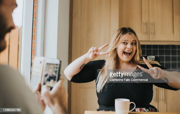 confident woman makes a v-sign with her hands as a man takes a photo on a phone - publicity event stock pictures, royalty-free photos & images