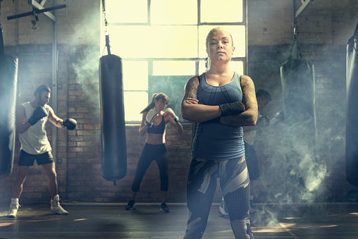Confident woman posing near punching bags in gymnasium - gettyimageskorea
