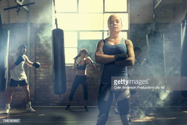 Confident woman posing near punching bags in gymnasium